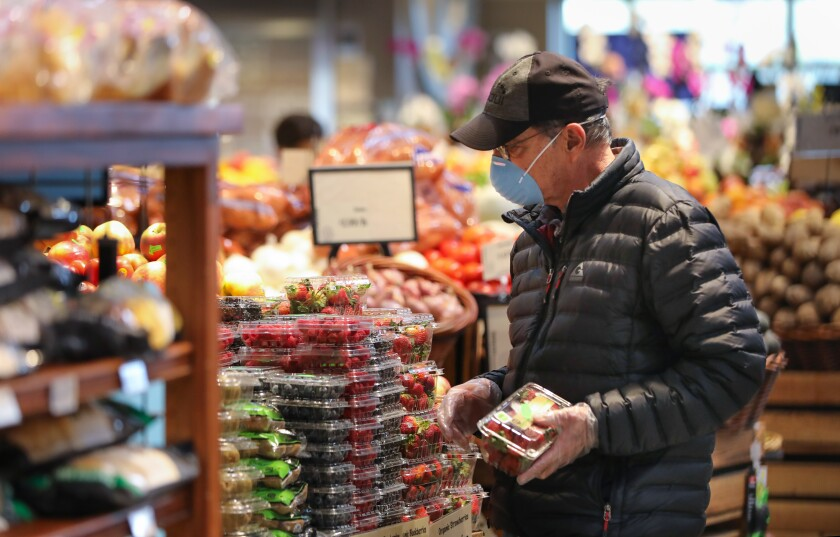 Conrad Kellenberger of North Park, wearing a face mask, shops in the Barons Market during the seniors-only time.