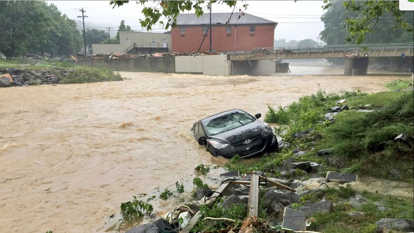 A vehicle is partially submerged in a stream after a heavy rain near White Sulphur Springs, W.Va., on June 24.