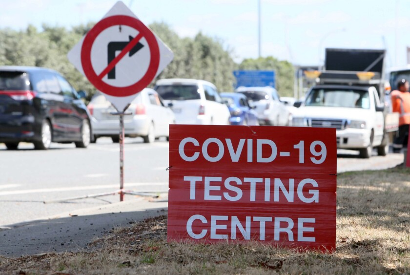 A coronavirus testing site with cars waiting in a line.