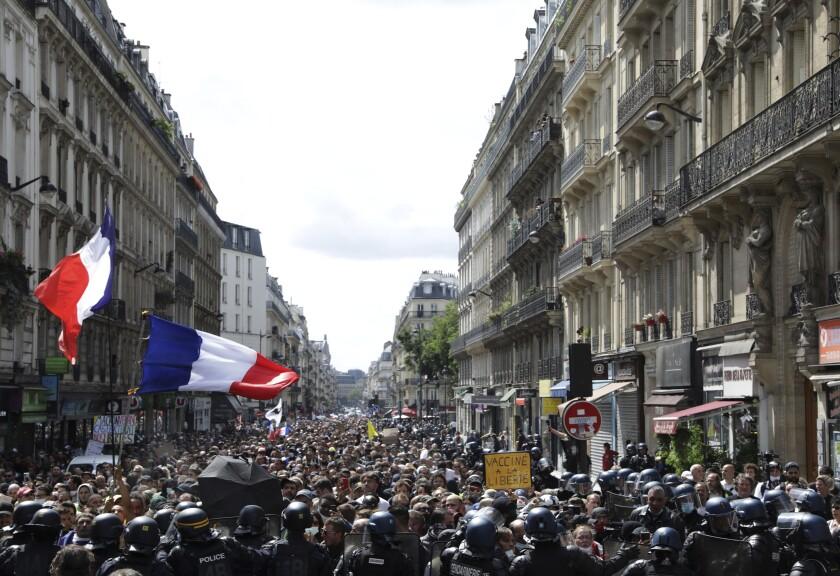 Banderas francesas ondean durante una marcha de miles de manifestantes en París, Francia, el sábado 31 de julio de 2021. (AP Foto/Adrienne Surprenant)