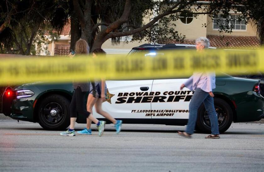 Un grupo de personas camina frente a la zona acordonada tras el tiroteo registrado en la escuela secundaria Marjory Stoneman Douglas de la ciudad de Parkland, en el sureste de Florida (Estados Unidos). EFE/Archivo