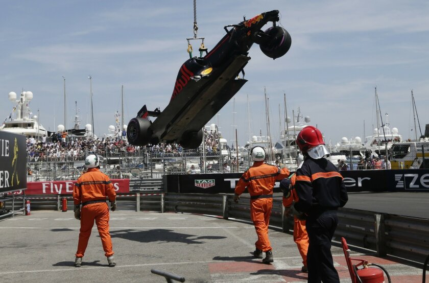 Track marshals remove car of Red Bull driver Max Verstappen of Netherlands, lifted from the track by a crane, after crashing during the qualification at the Monaco racetrack in Monaco, Monaco, Saturday, May 28, 2016. The Formula one race will be held on Sunday. (AP Photo/Petr David Josek)