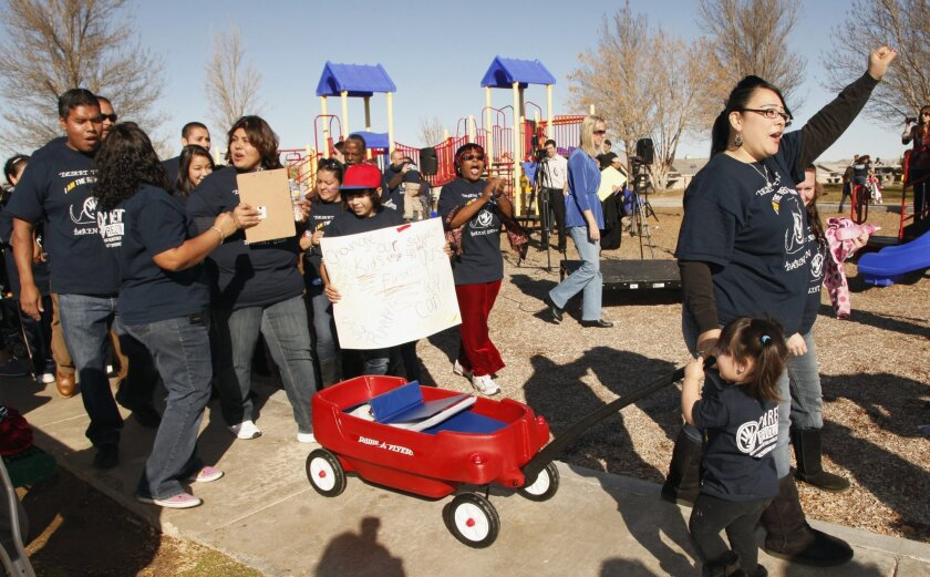 FILE - In this Jan. 12, 2012, file photo, parent Olivia Samaripa, far right, with her daughter Aria, 2, pull a wagon carrying petitions calling for their school to be converted to a charter school in the Mojave Desert town of Adelanto, Calif. More than 100,000 students in the nation's second-larges