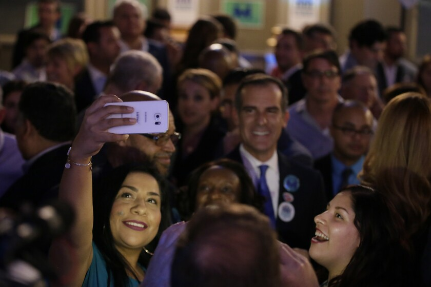 Sandra Lopez smiles for a selfie with Mayor Eric Garcetti during the Measure M party Tuesday night in downtown Los Angeles.