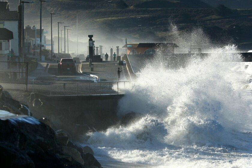 A wave pounds the shores of Pacifica during high tide.