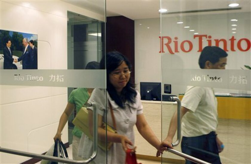 People leave a Rio Tinto office in Shanghai, China, Thursday, July 9, 2009. Four employees of miner Rio Tinto Ltd. who were detained on spying charges are accused of bribing Chinese steel company managers to obtain secret information on China's position in talks on iron ore prices, state media said Friday. (AP Photo)