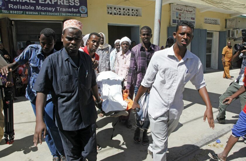 Relatives carry the dead body of a civilian who was killed by a mortar attack in the capital Mogadishu, Somalia, Thursday, Feb. 25, 2016. A Somali official says a mortar attack targeting the Somali presidential palace has killed three civilians, including a child. Police Capt. Mohamed Hussein said Thursday the mortars hit a residential area of the capital, Mogadishu. Al-Shabab militant group, an al-Qaida affiliate claimed the responsibility for the attack. (AP Photo/Farah Abdi Warsameh)