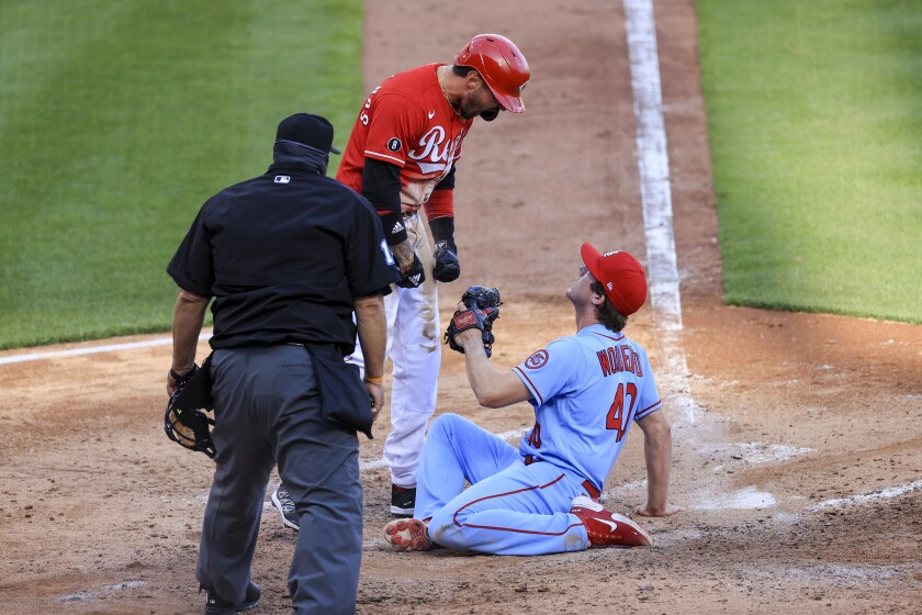 Cincinnati Reds' Nick Castellanos, center, reacts after scoring a run ahead of the tag by St. Louis Cardinals' Jake Woodford, right, during the fourth inning of a baseball game in Cincinnati, Saturday, April 3, 2021. (AP Photo/Aaron Doster)