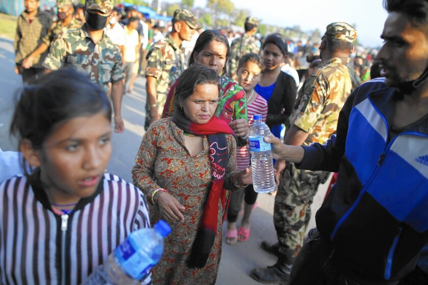 Nepalese earthquake survivors line up for food distribution in Katmandu, the capital, on May 13, a day after a 7.3 temblor, an aftershock from a larger quake in April.