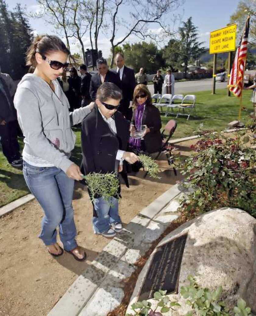 Yanette Posca, seated watches as family members sprinkle blessed water on a plaque for her husband Angel Posca and her youngest daughter Angelina, during a memorial service April 1, 2010.
