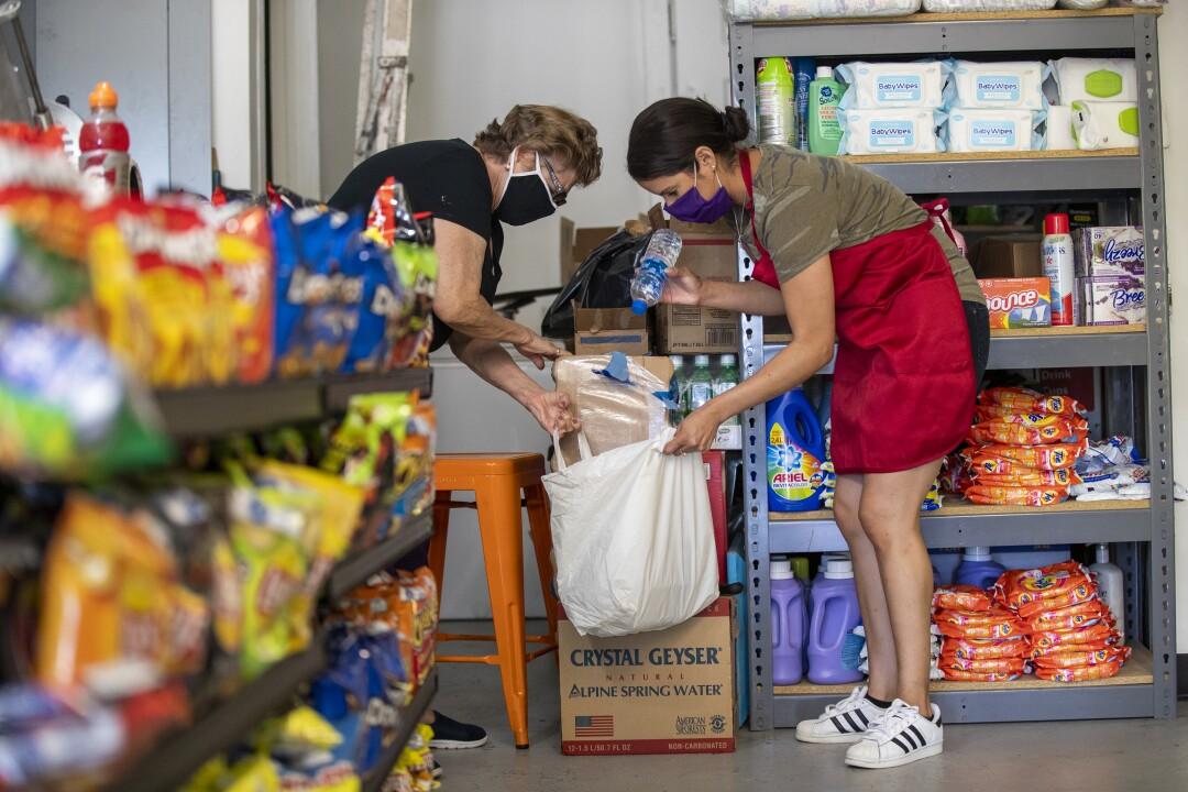Luz Arango, right, helps longtime customer Josefina Reynoso at Lupita's Corner Market.