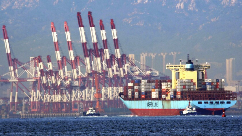 In this Oct. 8, 2018, photo, tugboats move a container ship to the dockyard of a seaport in Qingdao