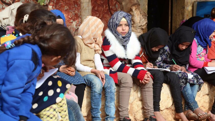 Syrian children who lost their parents in the country's civil war sit outside an orphanage near the town of Sarmada.
