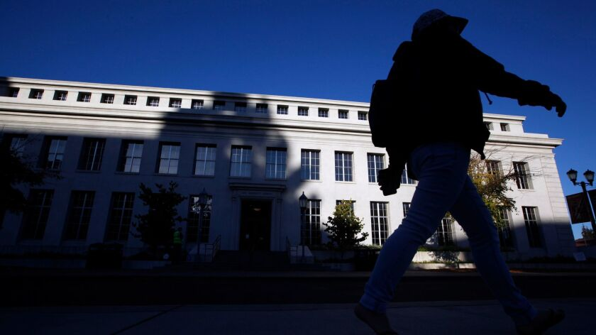 Student passes Bancroft Library in the early morning light on the campus of the University of California at Berkeley on Sept. 9, 2015.