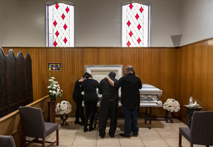 Several people wearing black huddle in front of an open coffin in a funeral home, heads bowed.