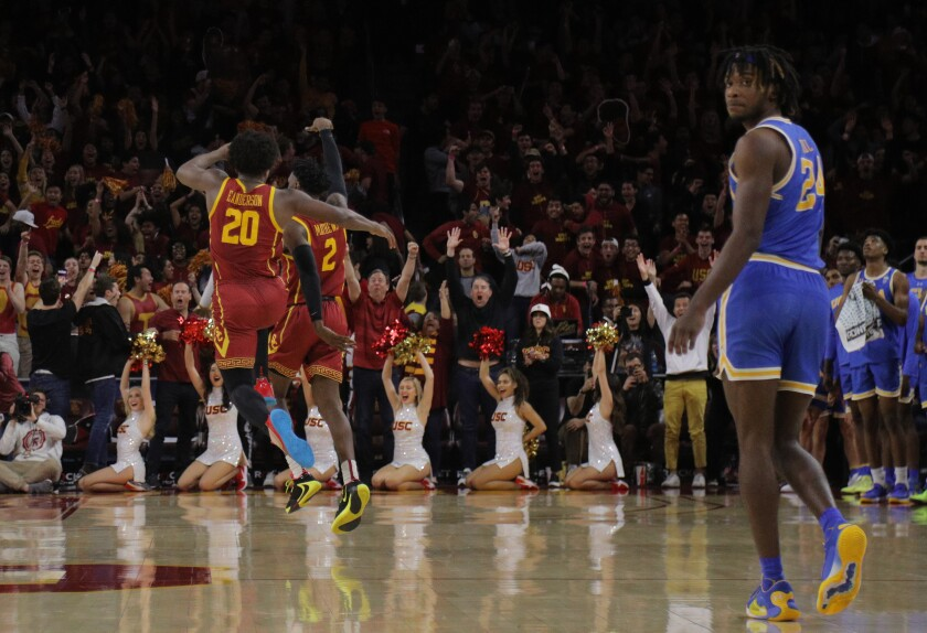 USC guard Jonah Mathews (2) reacts towards the crowd with guard Ethan Anderson (20) after scoring the game winning 3-point shot to beat UCLA in the final moments at Galen Center on Saturday.