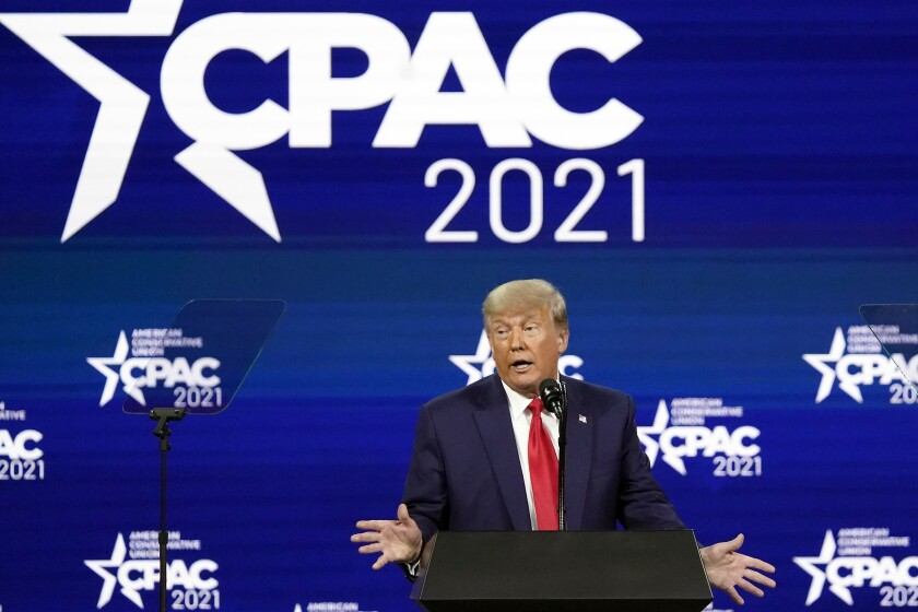 Former President Trump speaks at a lectern at the Conservative Political Action Conference.