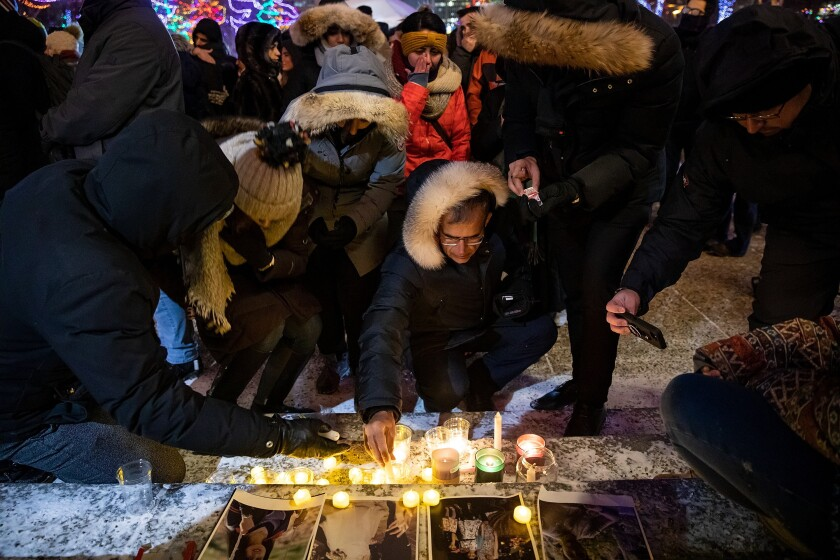 Mourners place candles and photographs outside the legislative building in Edmonton, Alberta, on Jan. 8, 2020, during a vigil for those killed after a Ukrainian passenger jet crashed, killing at least 63 Canadians, just minutes after takeoff from Iran's capital.