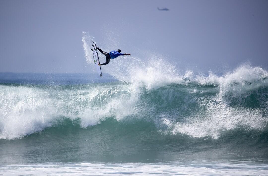 Italo Ferreira soars high over a big wave while competing against fellow countryman Filipe Toledo