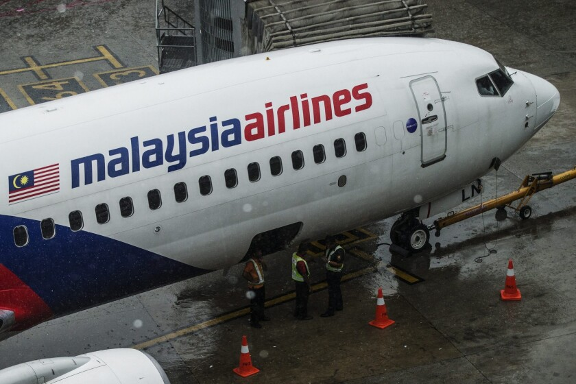 A Malaysia Airlines crew works near on an aircraft at Kuala Lumpur International Airport on Aug 8.