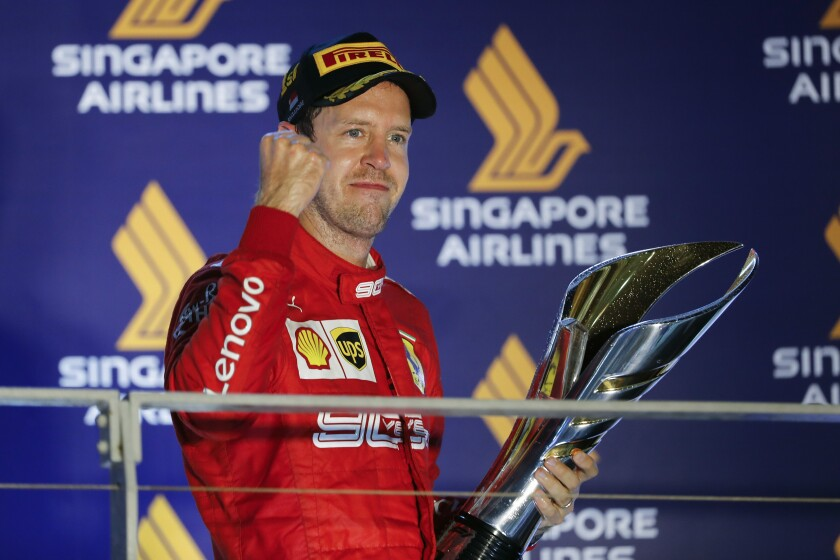Ferrari driver Sebastian Vettel celebrates with the trophy after winning the Singapore Grand Prix on Sunday.