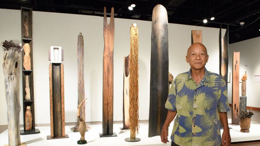 """Kenzi Shiokava stands by his totems on view as part of """"Transpacific Borderlands"""" at the Japanese American National Museum. The exhibition is one of the Pacific Standard Time shows to look at Asian artists in Latin America and the Caribbean."""