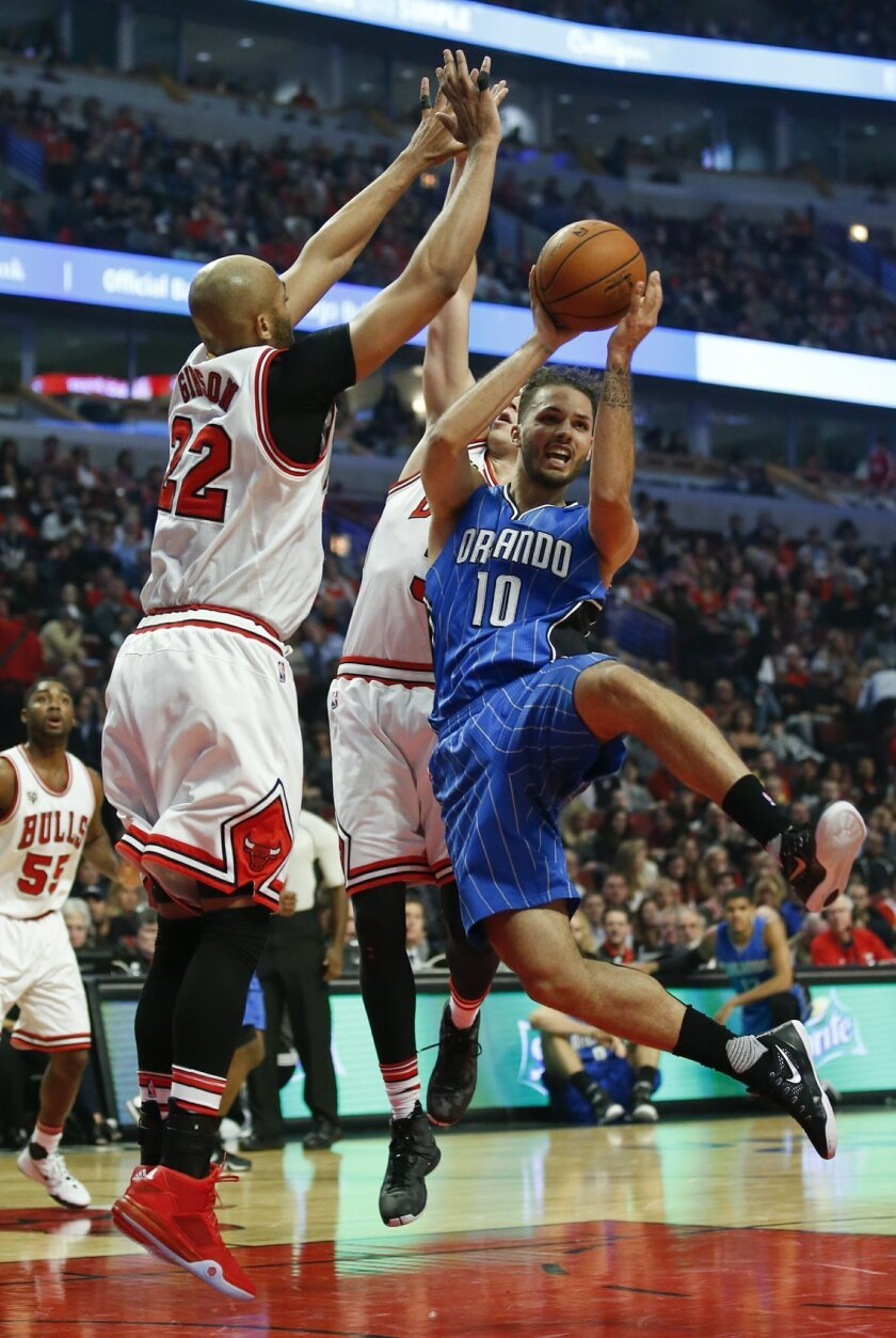 Orlando Magic guard Evan Fournier (10) looks to pass the ball away from Chicago Bulls forward Taj Gibson (22) and Chicago Bulls forward Doug McDermott, back, during the first half of an NBA basketball game, Sunday, Nov. 1, 2015, in Chicago. (AP Photo/Kamil Krzaczynski)
