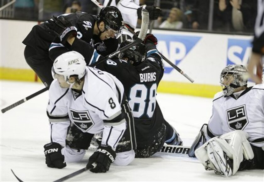 San Jose Sharks' Brent Burns (88) is congratulated by Logan Couture (39) after Burns scored a goal against Los Angeles Kings goalie Jonathan Quick, right, during the first period of an NHL hockey game Thursday, March 14, 2013, in San Jose, Calif. At left is Kings' Drew Doughty. (AP Photo/Ben Margot)