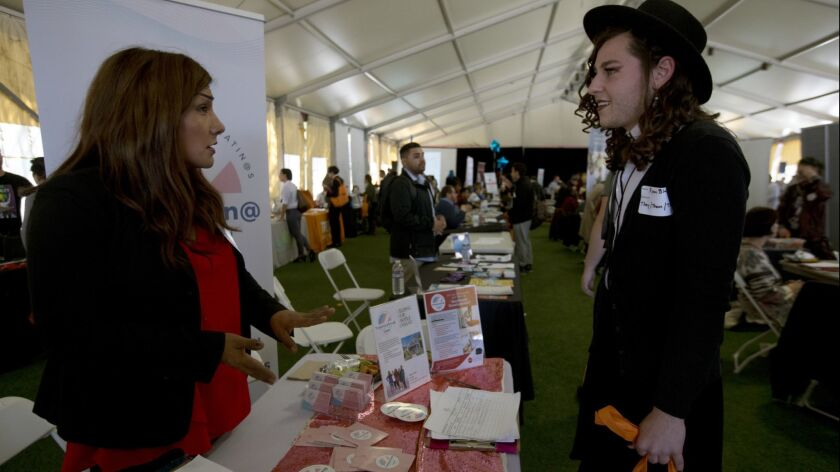 Ryan Blake, 22, right, speaks with an employer representative at the St. John's Well Child and Family Center job fair for the transgender community at Los Angeles Trade-Tech College on March 13.