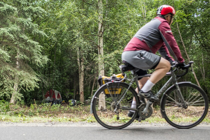 ANCHORAGE, ALASKA - Monday, August 6, 2018: A person bikes by a homeless camp off of the Chester Cre