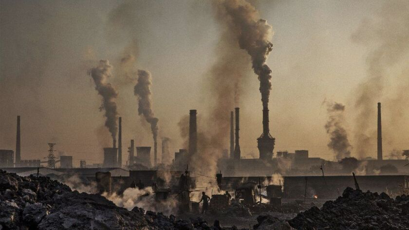 Smoke billows from a large steel plant as a Chinese labourer works at an unauthorized steel factory, foreground, on November 4, 2016 in Inner Mongolia