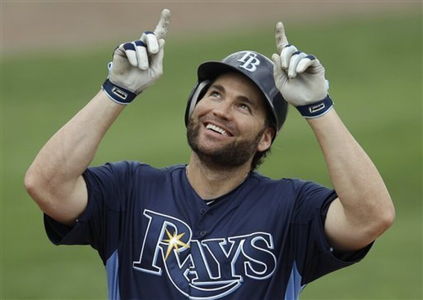 Tampa Bay Rays' Luke Scott celebrates after crossing home plate on a solo home run off Boston Red Sox pticher Tony Pena Jr. in the seventh inning of a spring training baseball game in Port Charlotte, Fla., Saturday, March 31, 2012. (AP Photo/Charles Krupa)