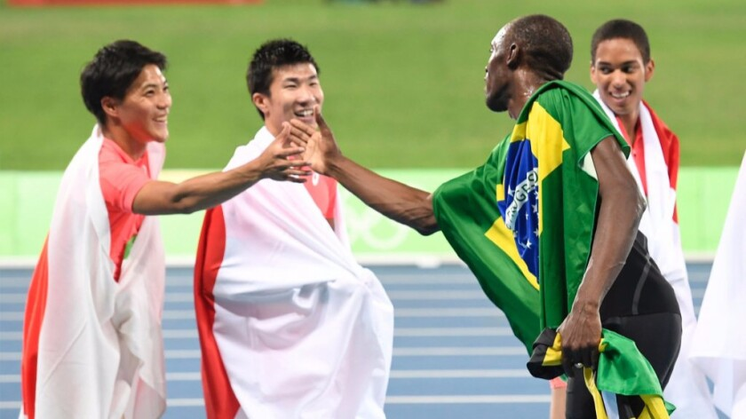 Jamaican sprinter Usain Bolt, right, shakes hands with Japanese runners on Aug. 19 at the Olympic Games in Rio de Janeiro. A new study finds surprising shared sound patterns across unrelated languages around the world.