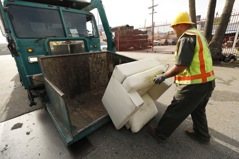 A sanitation worker loads a chair for removal