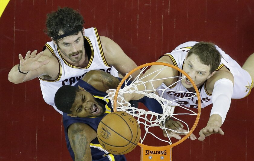 Indiana Pacers forward Paul George, center, scores against Cleveland Cavaliers forward Kevin Love, left, and center Timofey Mozgov during the first half of an NBA basketball game Sunday, Nov. 8, 2015, in Cleveland. (AP Photo/Ron Schwane)