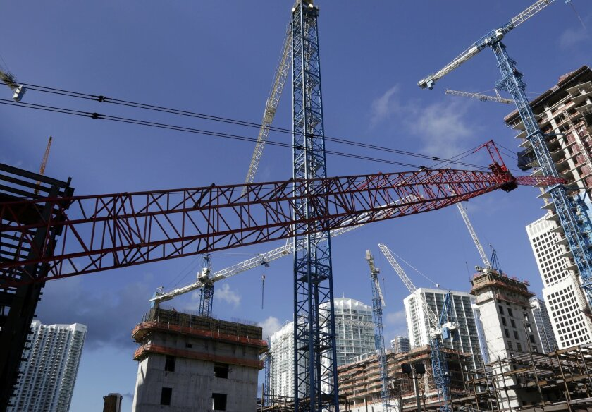 This Thursday, July 24, 2014 photo shows construction cranes at the Brickell City Centre project in downtown Miami. According to real estate license applications in 2013, the number of U.S. real estate agents is increasing as the housing market recovers from the Great Recession. (AP Photo/Lynne Sladky)