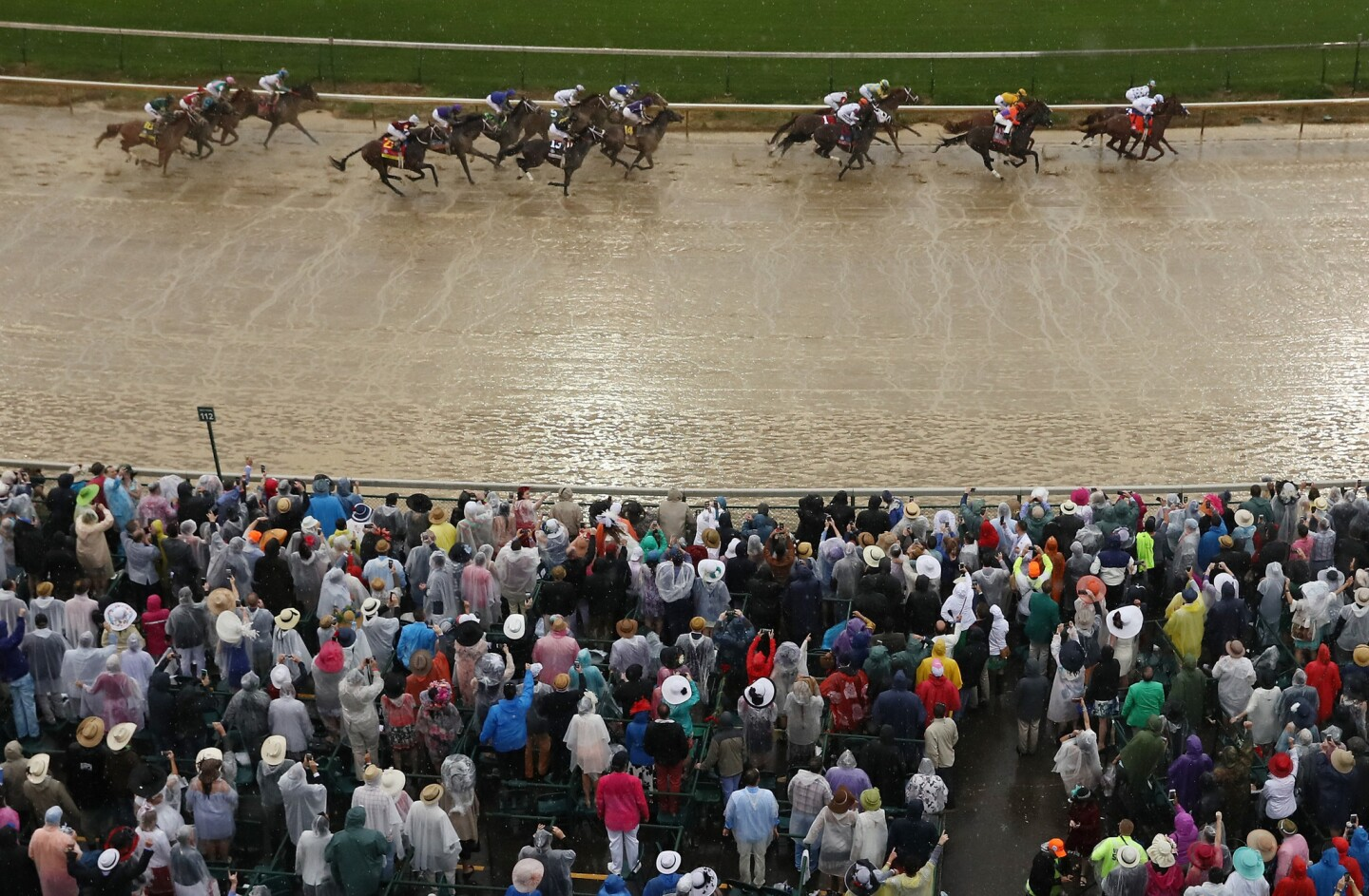 Spectators watch Promises Fulfilled, ridden by jockey Corey Lanerie, and Justify, with Mike Smith aboard, lead the field into the first turn during the 144th running of the Kentucky Derby.