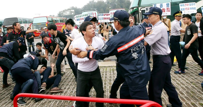 Anti-unification protesters clash with police as Chinese negotiators hold talks in the Golden Lake Hotel on Kinmen Island on Saturday.