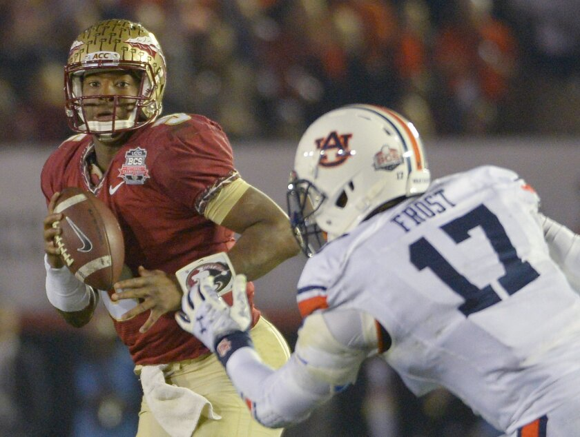 Florida State's Jameis Winston looks to pass with Auburn's Kris Frost defending during the second half of the NCAA BCS National Championship college football game Monday, Jan. 6, 2014, in Pasadena, Calif. (AP Photo/Mark J. Terrill)