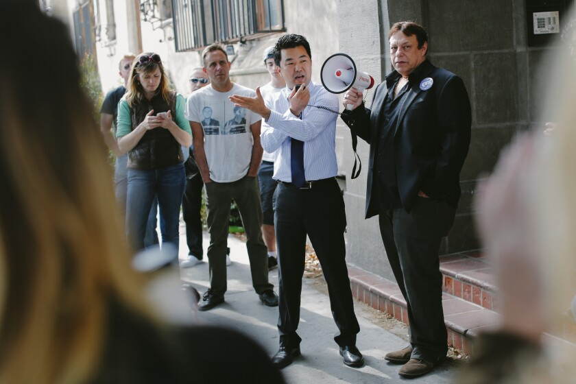 Then-L.A. City Council candidate David Ryu speaks in 2015 at a rally organized by Larry Gross, right, with the Coalition For Economic Survival, for residents of the Villa Carlotta apartment building in Hollywood.
