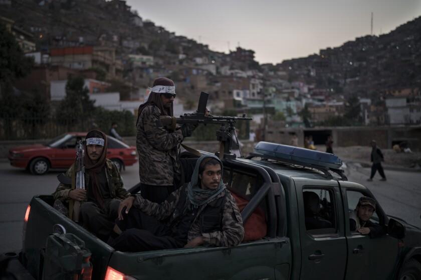 Combatientes talibanes, sentados en la parte de atrás de una camioneta, durante una parada
