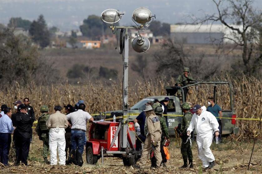 Expertos canadienses trabajan hoy en la zona en la que se desplomo una aeronave el pasado 24 de diciembre, en el municipio de Coronango, Puebla (México). EFE/Archivo