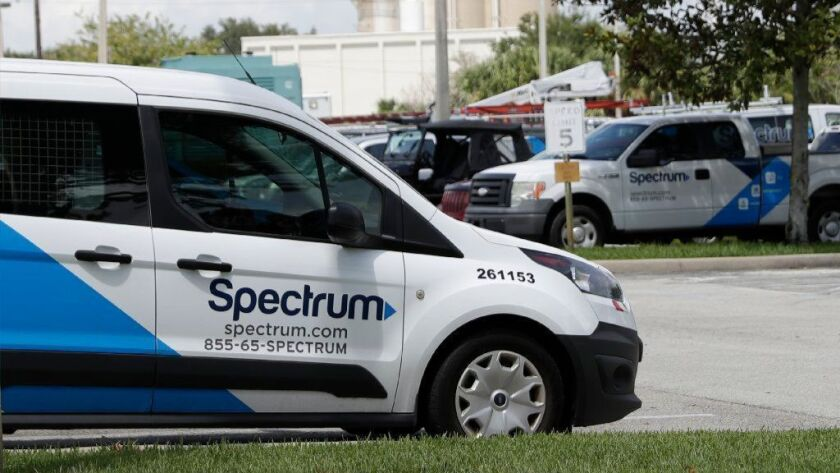 Spectrum trucks are parked at a customer center in Orlando, Fla., in September.