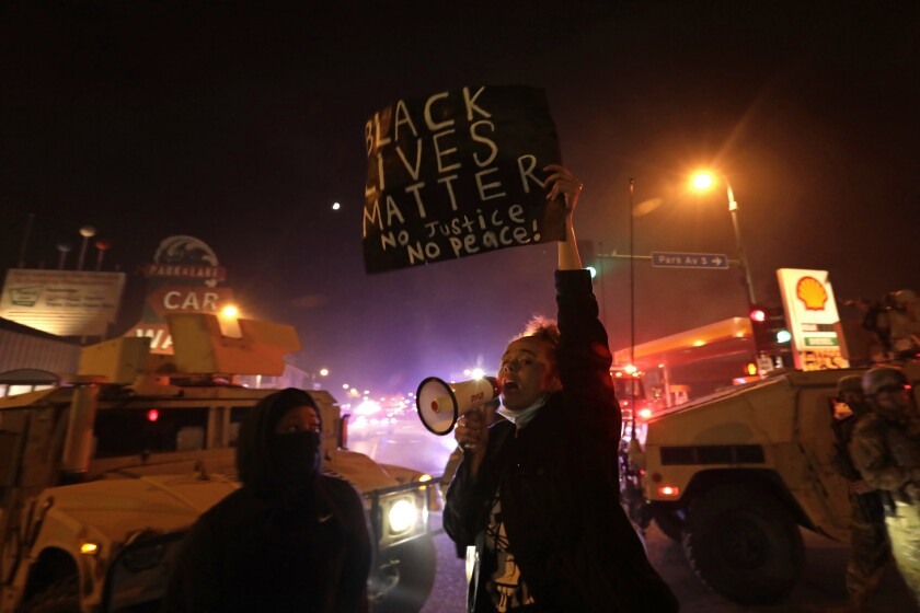 Protesters defy a curfew order in Minneapolis on Friday night.