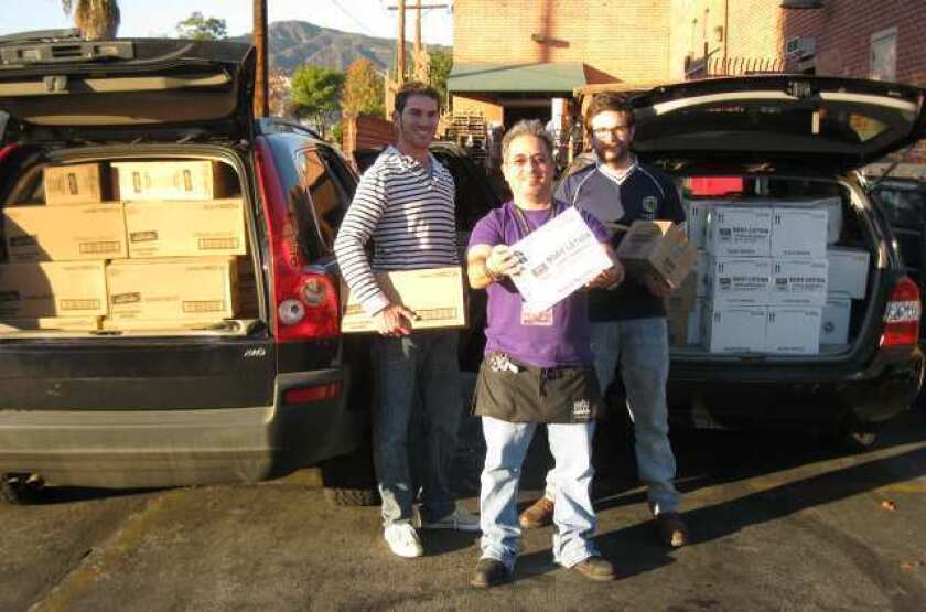 Loading up donations for Ascencia are volunteer Steven John, from left, Whole Foods cashier Miguel Gonzalez, who has personally raised more than $3,000 from his customers, and volunteer Josh Grayson.