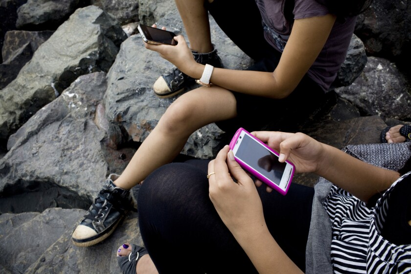 College students use their smartphones in Mumbai, India. A UNESCO study has found that people are reading more books, thanks to the spread of smartphone technology in developing countries.