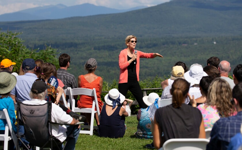 Sen. Elizabeth Warren standing in a field with a microphone speaking to a crowd seated in front of her