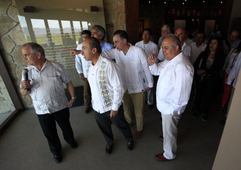 President Felipe Calderon, center, during a tour of the new wine museum in the Guadalupe Valley, with Baja California Gov. Jose Guadalupe Osuna Millan, right.