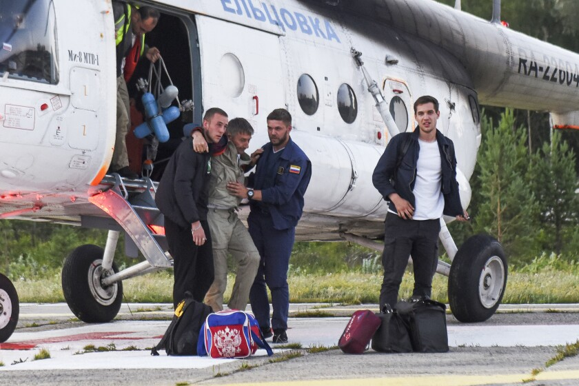 Anatoly Prytkov, a pilot of the An-28 plane, which made an emergency landing, helped by his colleagues to exit a helicopter carrying passengers of the An-28 at an airport outside in Tomsk, Russia, Friday, July 16, 2021. Emergency officials say a small Russian passenger plane has made an emergency landing in Siberia after an engine failure. None of the 18 passengers and crew members suffered serious injuries. The An-28 plane went missing Friday in the Tomsk region in western Siberia. (Taisya Vorontsova/RIA Tomsk via AP)