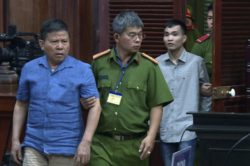 """Australian man Chau Van Kham, left, is escorted into a court room in Ho Chi Minh city, Vietnam Monday, Nov. 11, 2019. Kham was sentenced to 12 years in jail for conducting activities of """"terrorism to oppose the people's administration."""" (Nguyen Thanh Chung/VNA via AP)"""